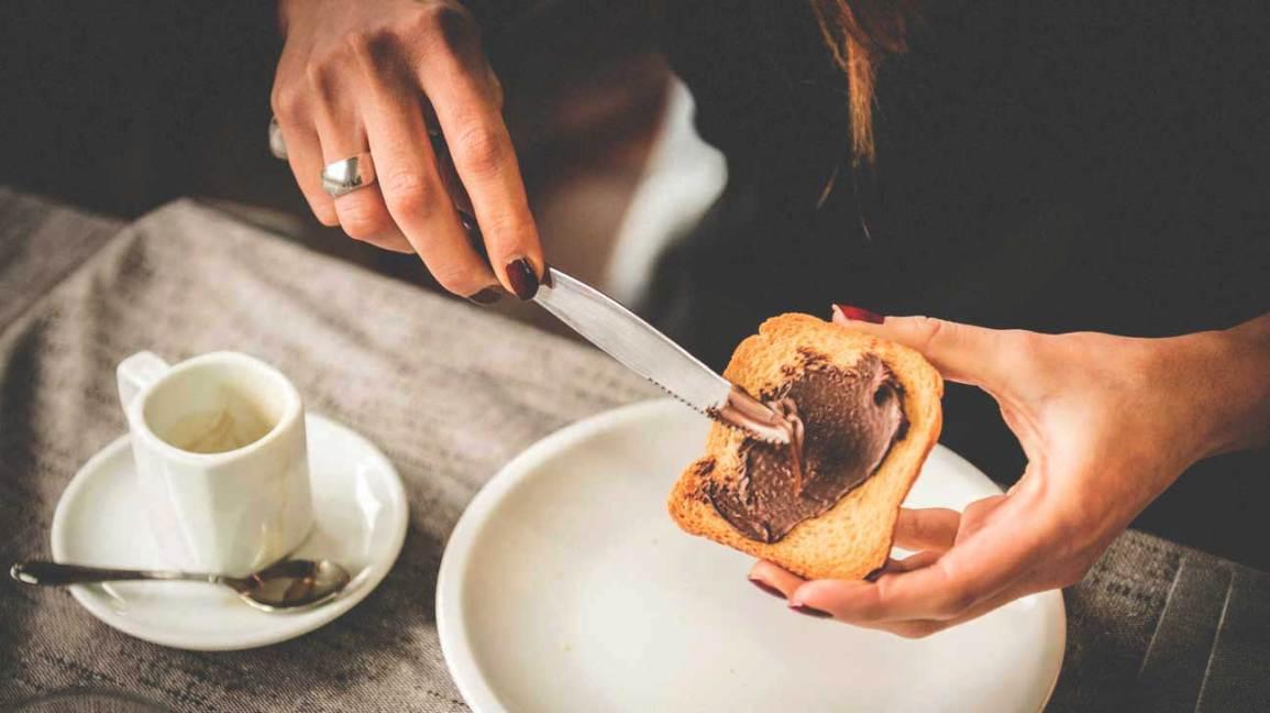 Femme répandant du Nutella sur du pain grillé