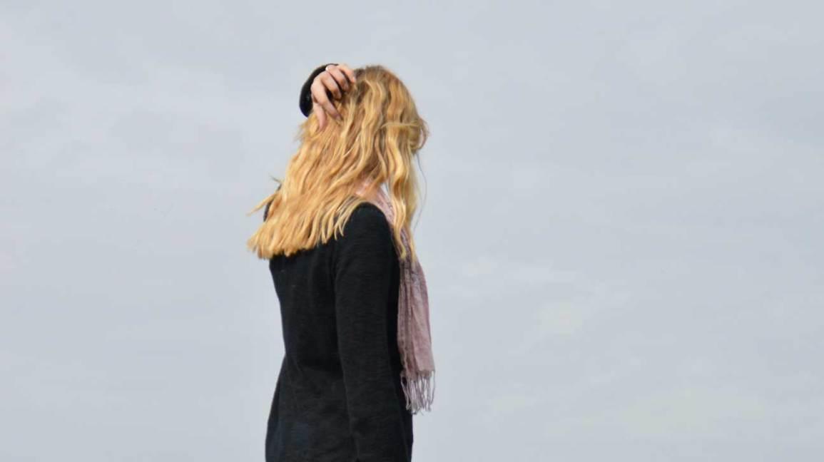 Femme debout près du mur gris