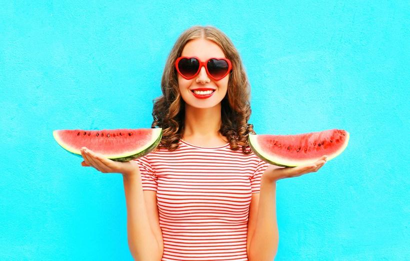 Sourire femme tenant la pastèque dans chaque main