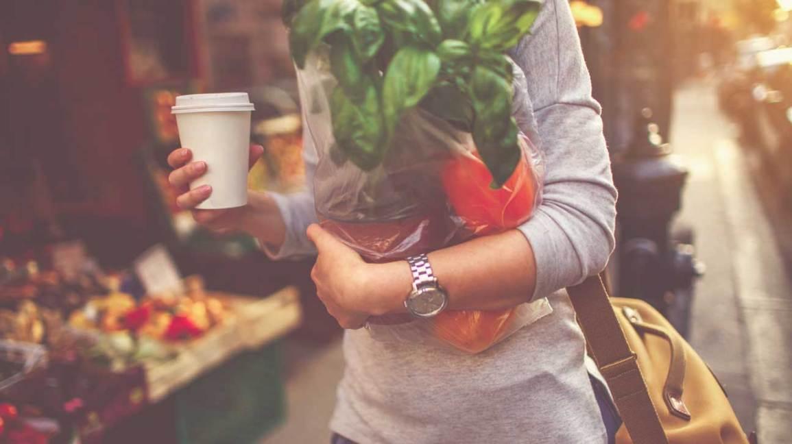 Femme tenant un café et des légumes