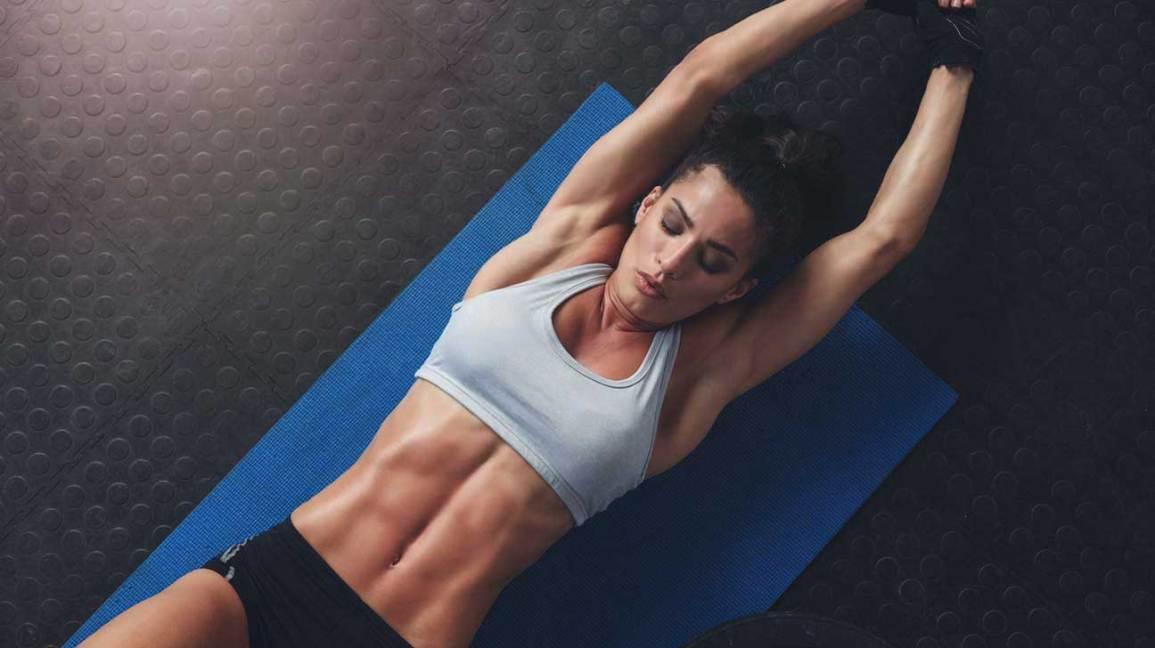 Fit femme allongée sur un tapis de yoga
