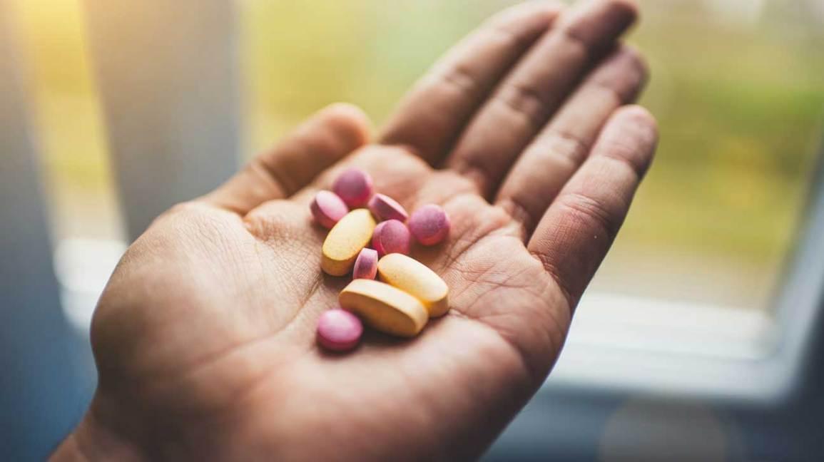 Hand, welche die gelben und rosafarbenen Pillen anhält
