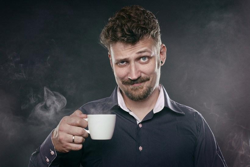 Homme sceptique tenant une tasse de café
