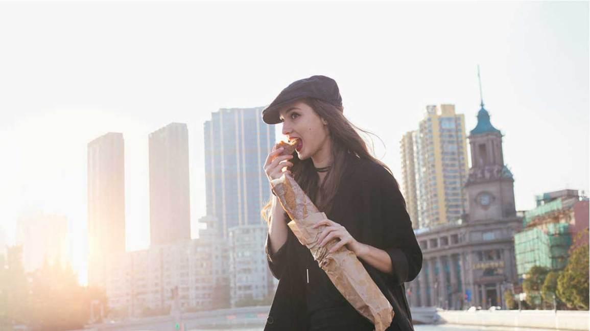 Femme mangeant une baguette en ville
