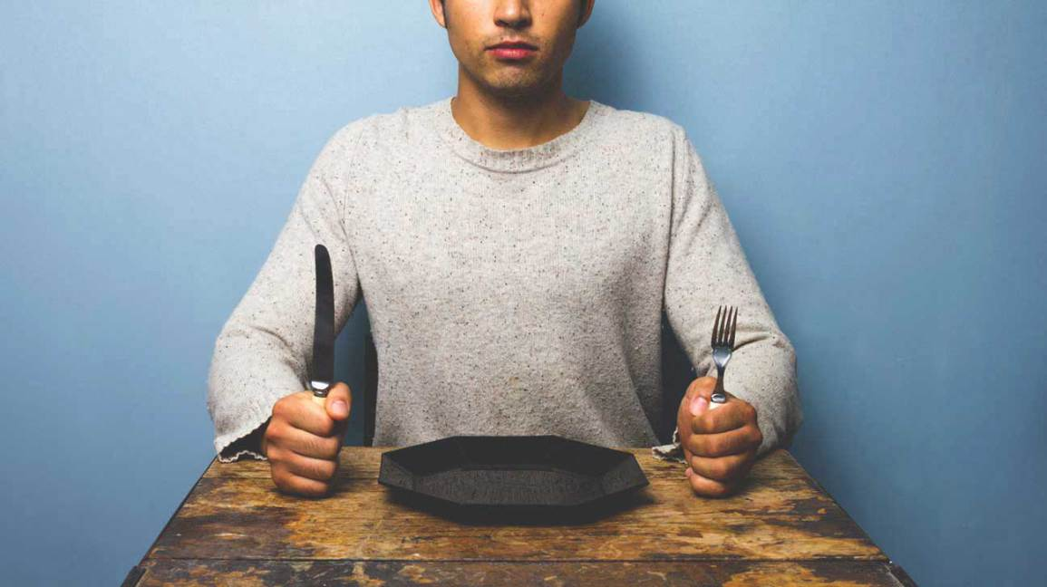 Homme assis à table avec assiette vide