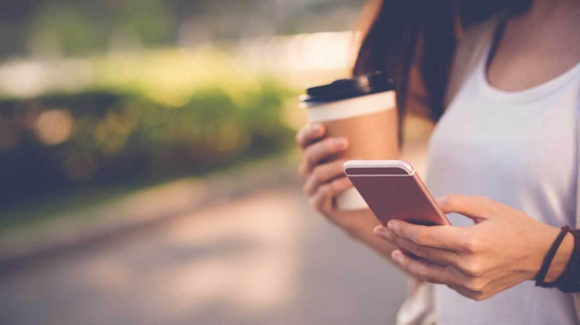 Femme tenant un téléphone et un café