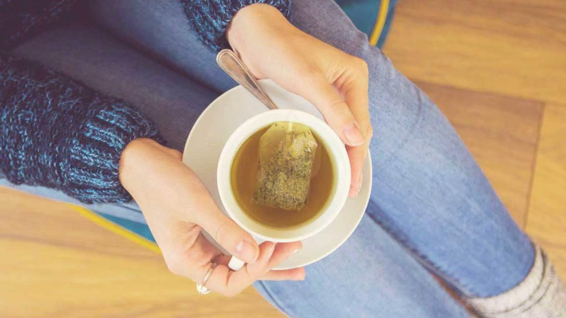 Hält eine Tasse grünen Tee