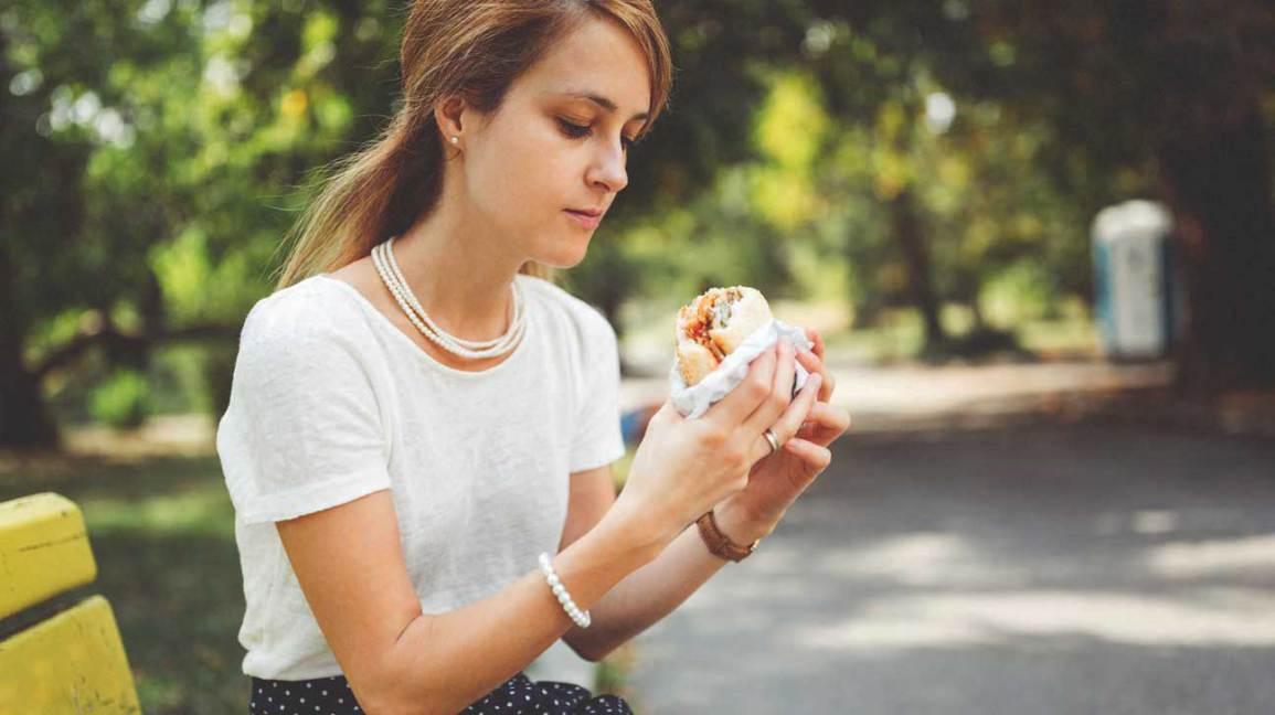 Jeune femme manger burger