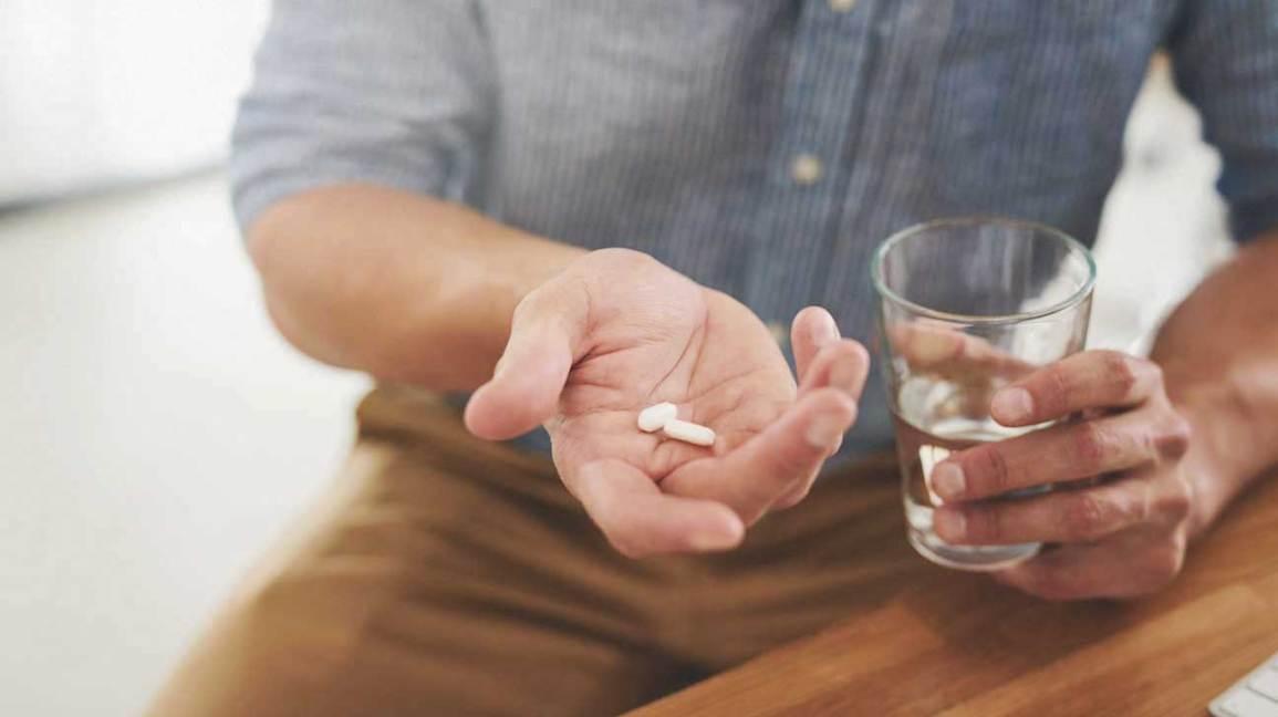 Homme tenant des pilules et un verre d'eau
