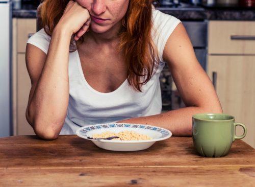 Femme regardant s'ennuyer à regarder bol de céréales - perte de poids malsaine