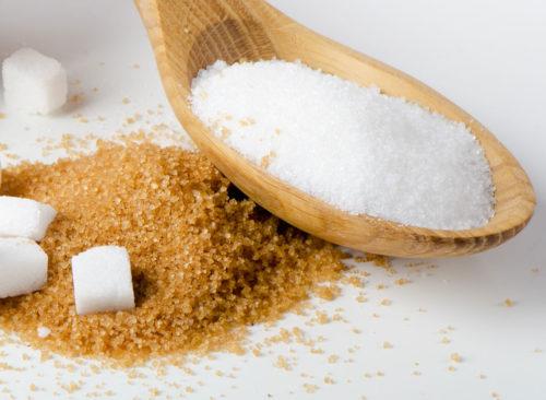 Sucre blanc dans une cuillère en bois reposant sur du sucre brun - perte de poids malsaine