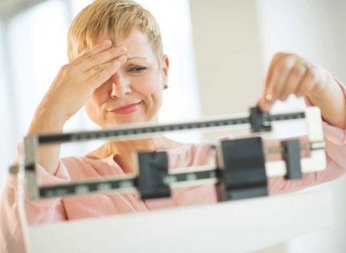 Malheureuse femme sur une balance - perte de poids malsaine