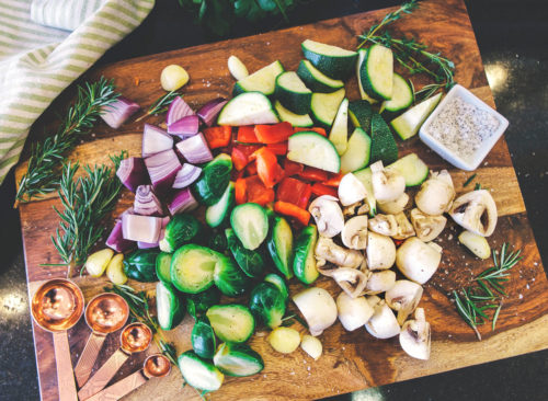 Préparation de repas légumes hachés choux de bruxelles oignons champignons poivrons courgettes sur une planche à découper en bois - perte de poids malsaine