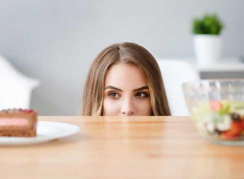 Femme avide de malbouffe devant une salade - perte de poids malsaine