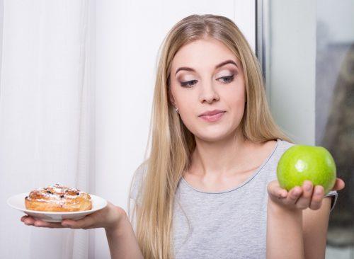 Femme choisissant pomme au-dessus d'une pâtisserie au sucre - perte de poids malsaine