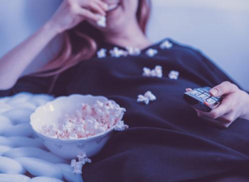 Femme mangeant du pop-corn à la télévision