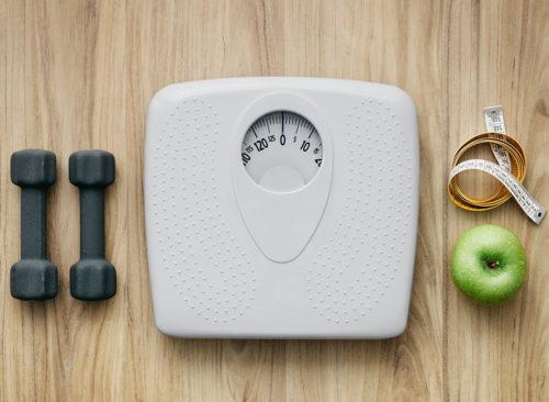 Haltères assis à côté d'une balance avec ruban à mesurer et une pomme verte