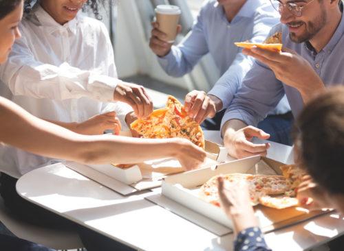 Les collaborateurs attrapent rapidement des tranches de pizza au travail