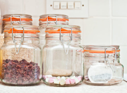 Bonbons et collations visibles dans des récipients en verre transparents sur la table de la cuisine