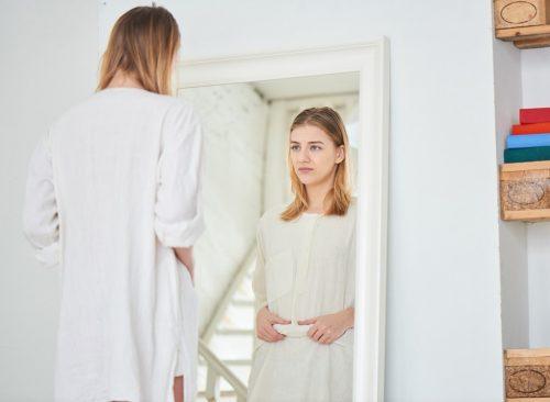 Femme se regarde dans le miroir