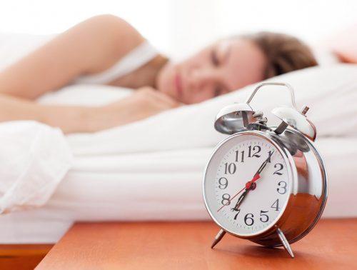 Femme au lit avec réveil