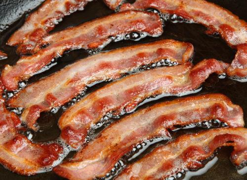 bacon gras frit dans l'huile dans une casserole