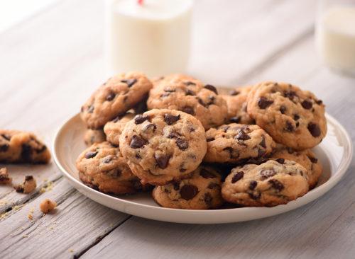 Cookies aux pépites de chocolat sur une assiette avec deux tasses de lait en arrière-plan