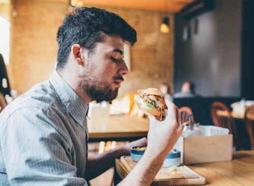 Guy mange au restaurant rapide