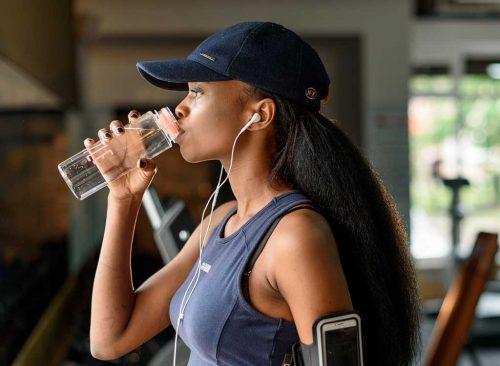 Femme buvant de l'eau au gymnase