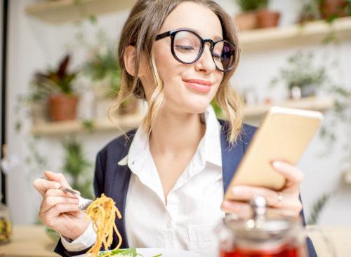 Femme mange avec téléphone