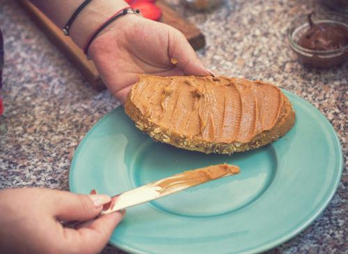 Femme, répandre, beurre cacahuète, sur, pain
