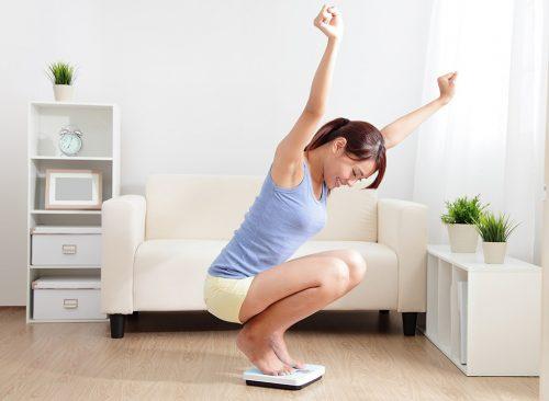 La femme sur une balance célèbre sa perte de poids