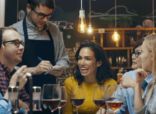 le serveur prend des notes pour les groupes d'amis avec des boissons