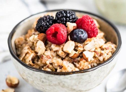 Fruits d'avoine à fibres complètes avec de l'avoine, des baies fraîches, des noix et des graines - comment battre le plateau de la perte de poids