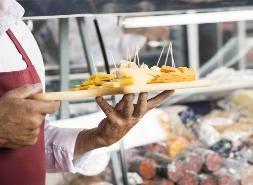 Homme tenant plateau de fromage par des échantillons gratuits en épicerie