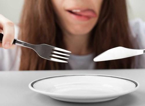 Assiette vide de couteau fourchette femme affamée
