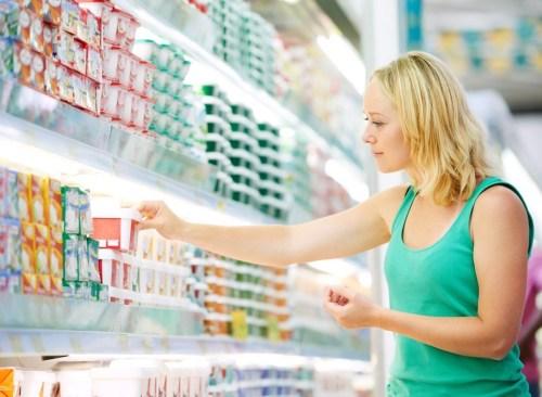 Une femme atteint l'étagère pour récupérer un article à l'épicerie