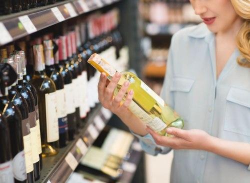 Femme regardant l'étiquette d'une bouteille de vin à acheter