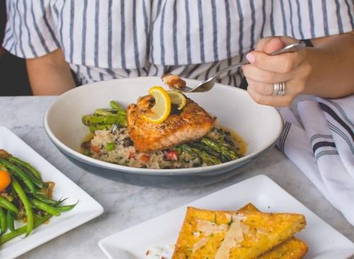 Femme mangeant du saumon - Comment se débarrasser d'un estomac gonflé en 24 heures