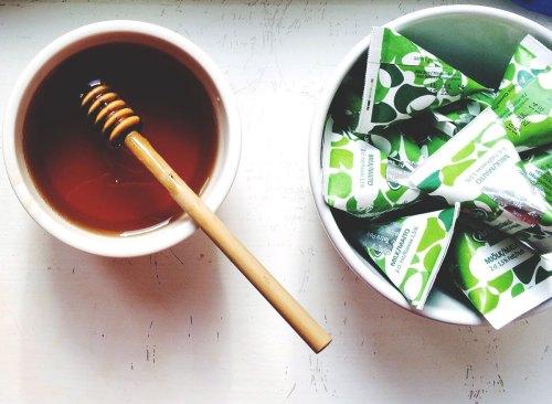 Le miel dans un bol à côté d'un bol de sachets de sucre - comment se débarrasser de l'estomac gonflé en 24 heures
