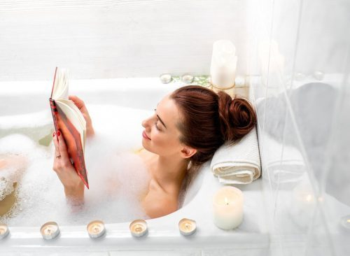 Femme lisant dans une salle de bain
