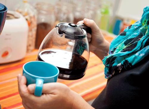 femme tenant une cafetière et une tasse - comment se débarrasser d'un ventre gonflé en 24 heures