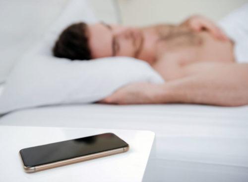 Homme dormant, téléphone, table de chevet