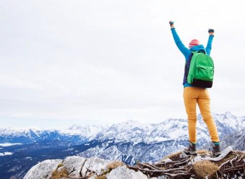 Un alpiniste se réjouit au sommet de la montagne