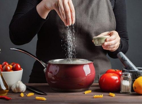 les mains ajoutent du sel dans l'eau des pâtes