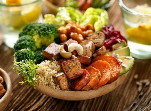 Bol de Bouddha contenant des aliments à base de plantes, notamment du brocoli, des noix, du tofu, des carottes, de l'avocat et bien plus encore