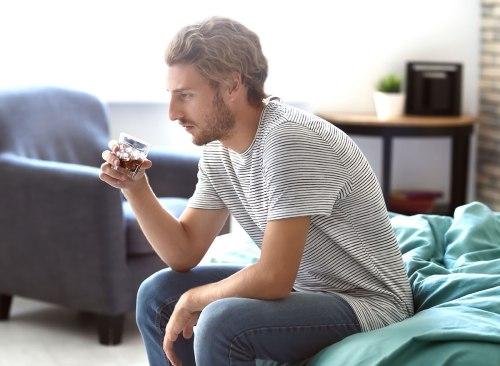homme assis sur un lit avec un verre d'alcool - Comment l'alcool affecte-t-il le cerveau?