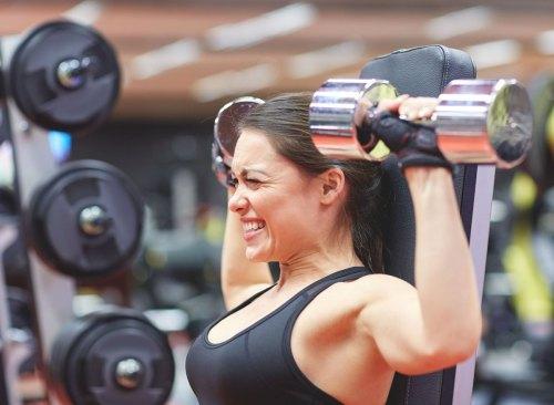 Une femme s'efforce de soulever des poids au gymnase à cause d'une perte de masse musculaire