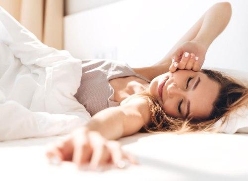 Femme se réveillant d'une nuit tranquille dans son lit