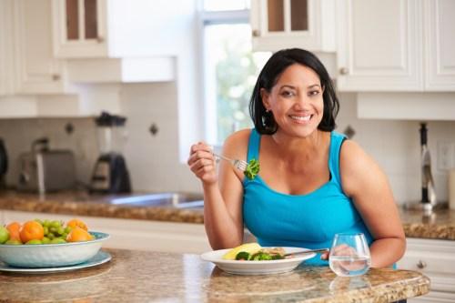 Femme mangeant des repas sains dans la cuisine
